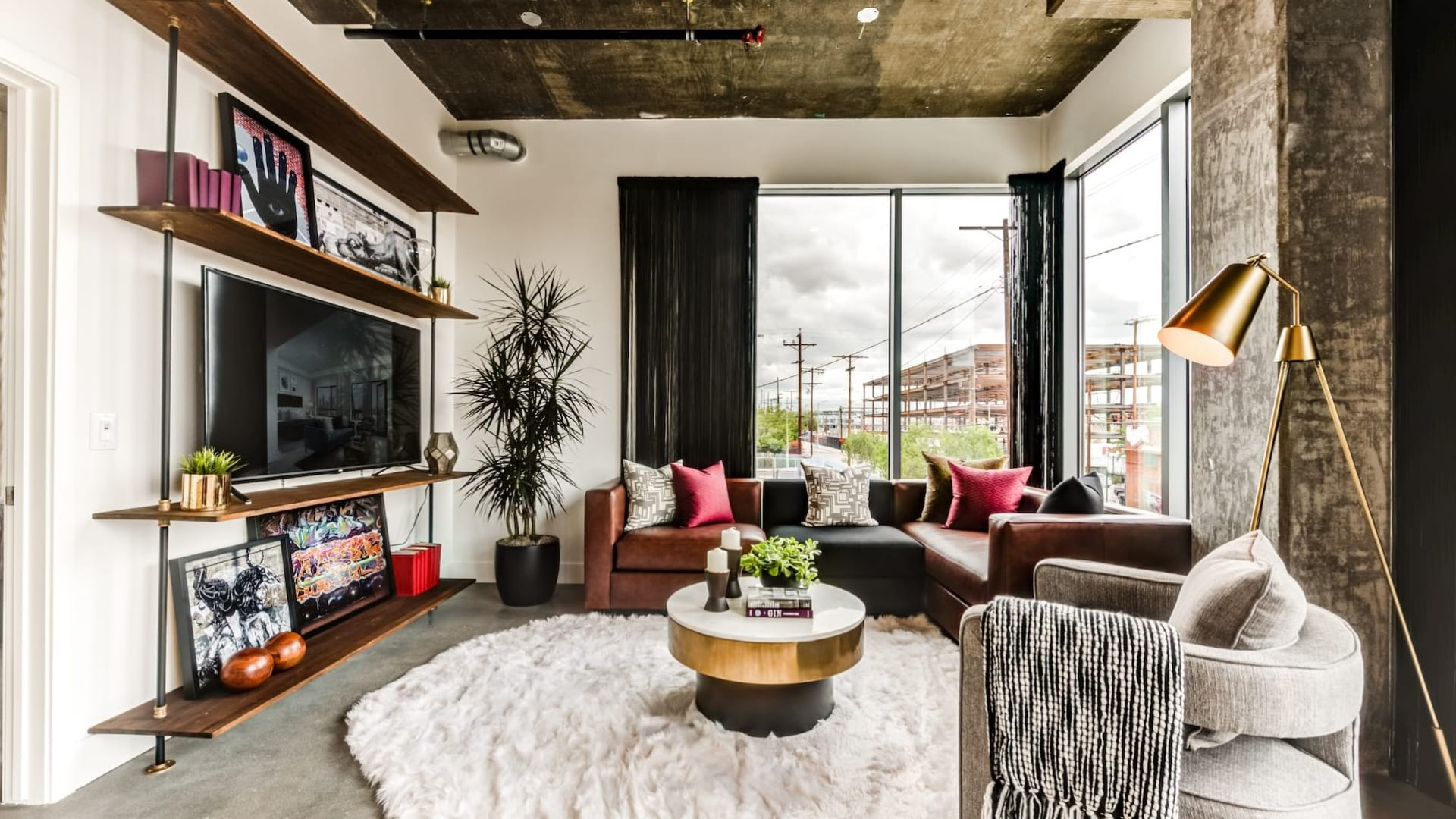 AMP Lofts LA furnished living room with large windows and concrete floors