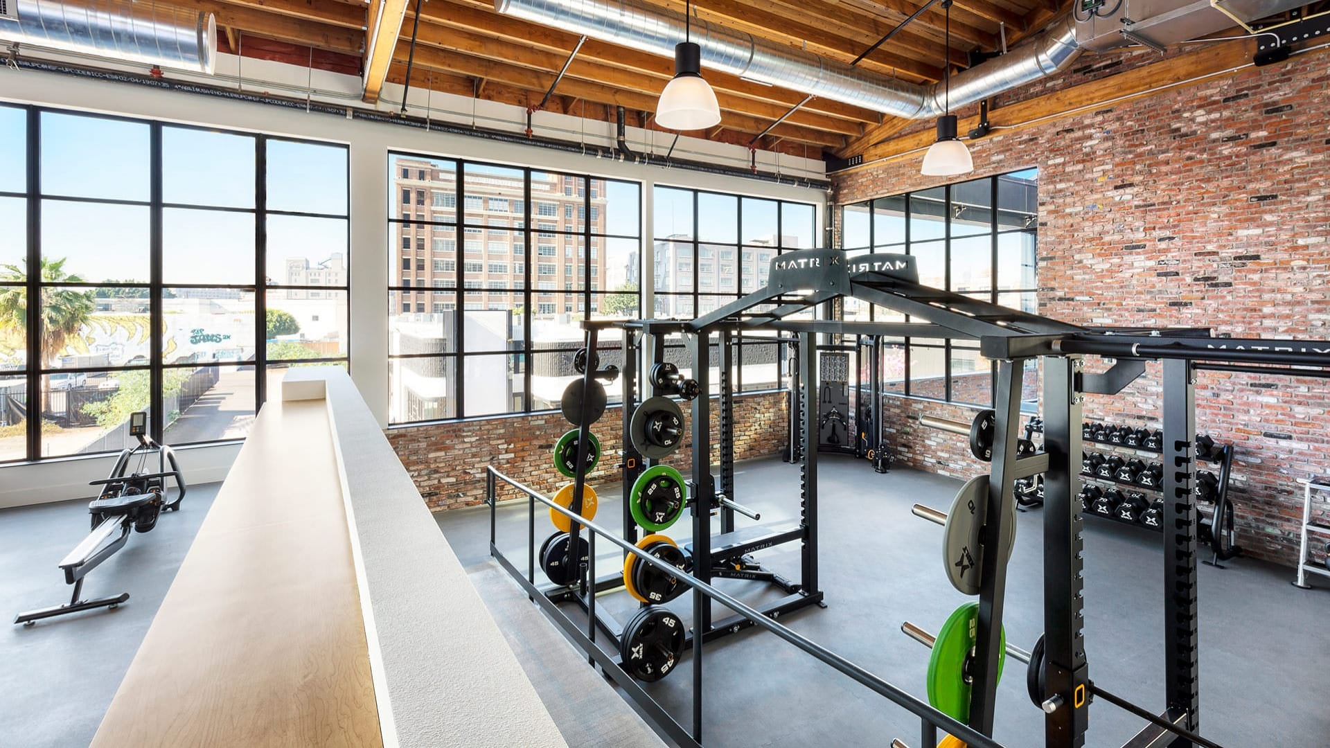 free weight area in fitness center with massive windows