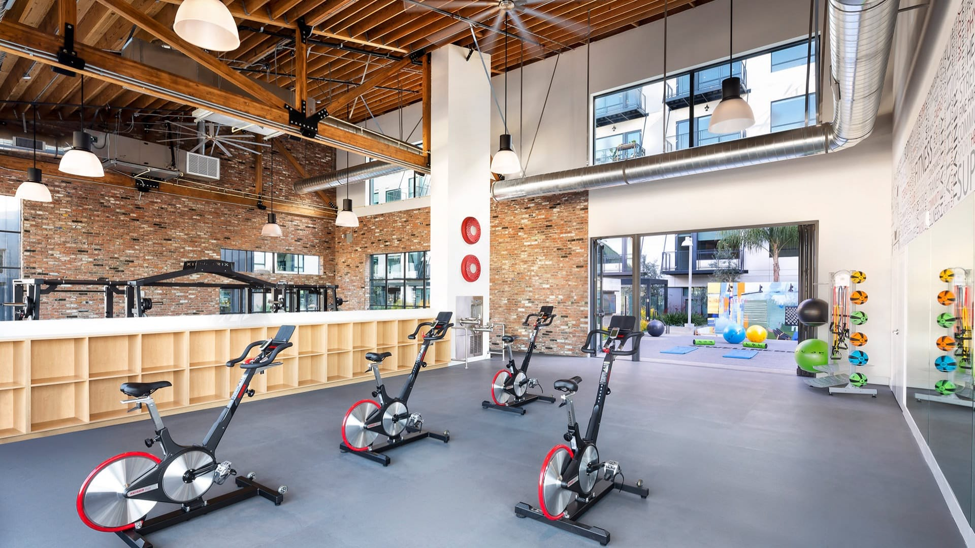 spin cycles in fitness center with exposed ceiling beams and air ducts
