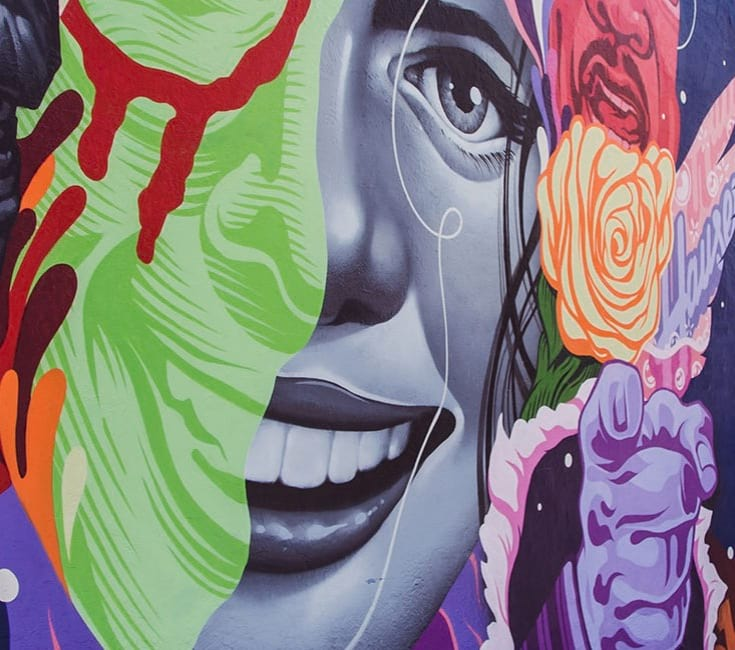 Colorful wall art with a woman's face and a hand pointing